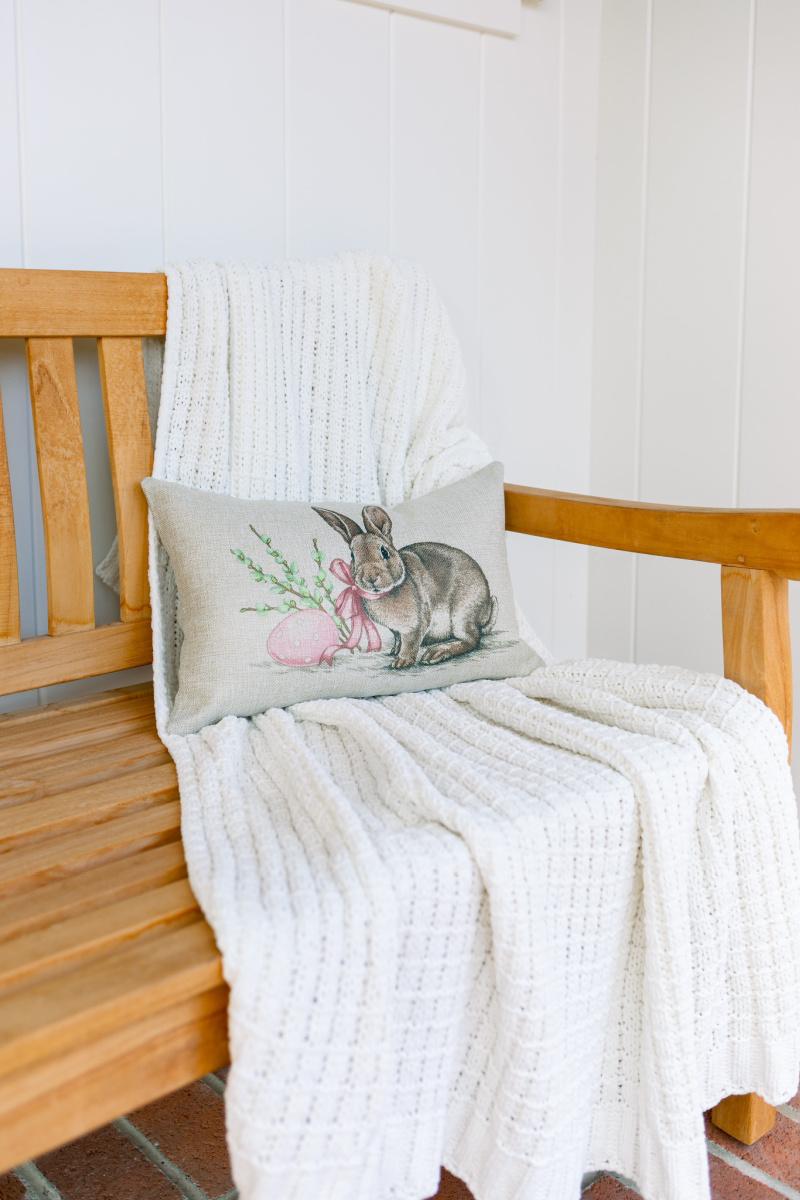 Bunny lumbar pillow on teak bench