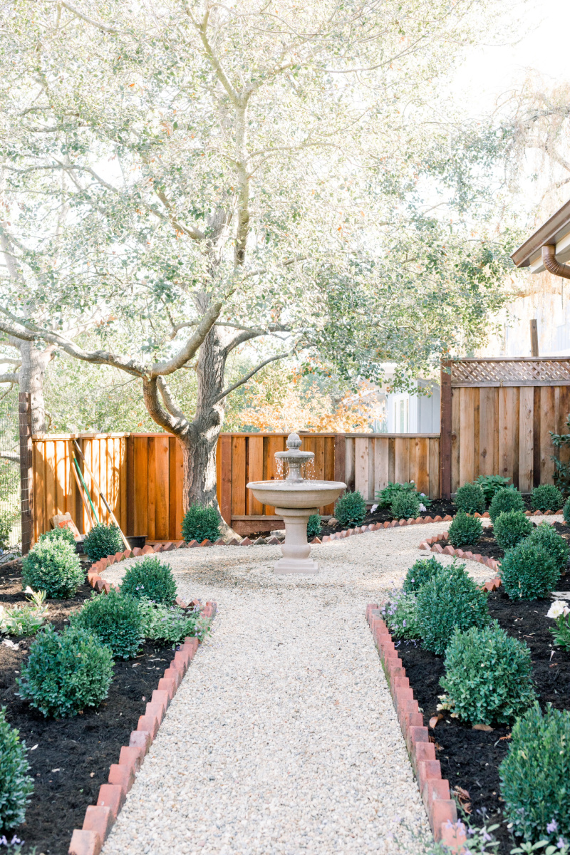 Garden gravel path lined with brick leading to fountain