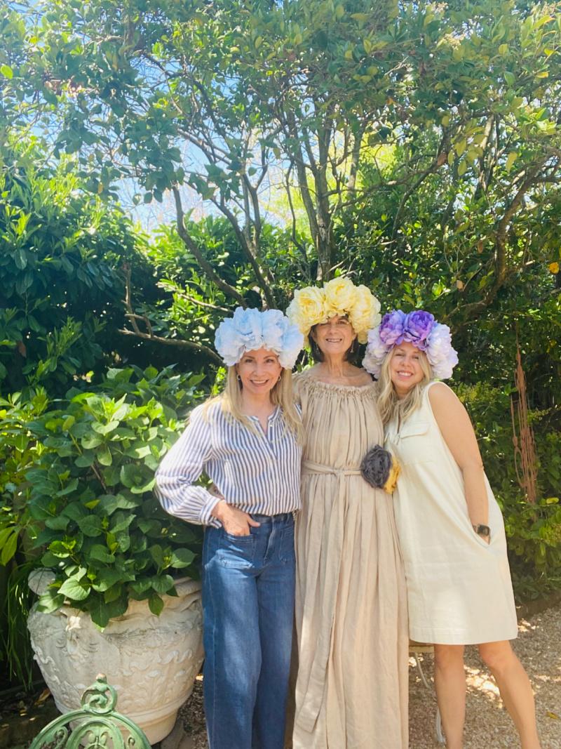 Three women wearing flower crowns in the garden