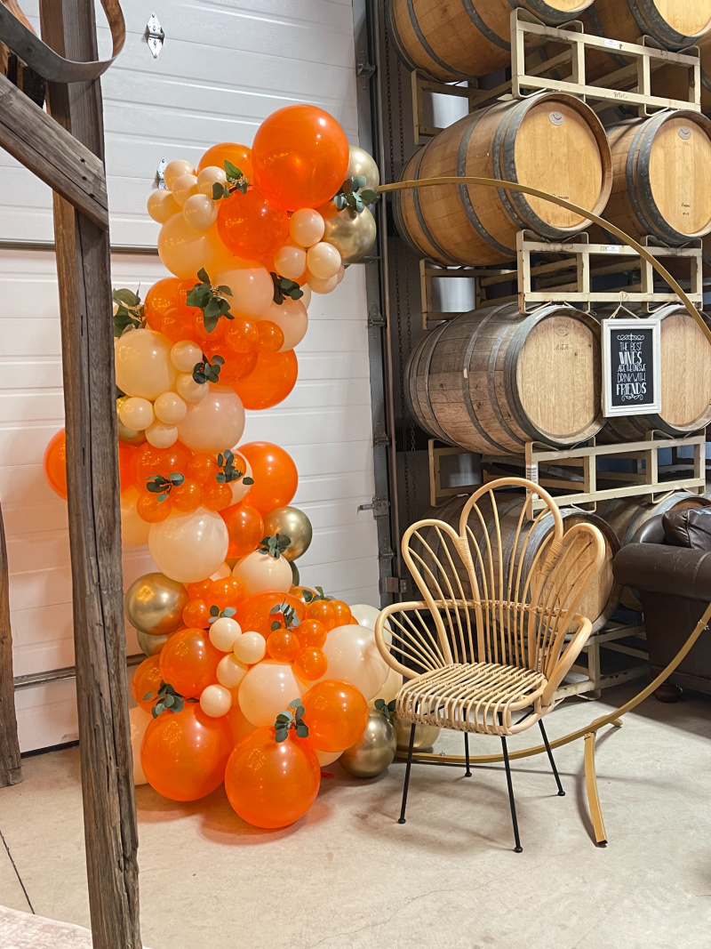 Orange balloon garland and fan back chair