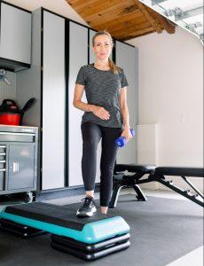 Woman holding hand weight in garage gym