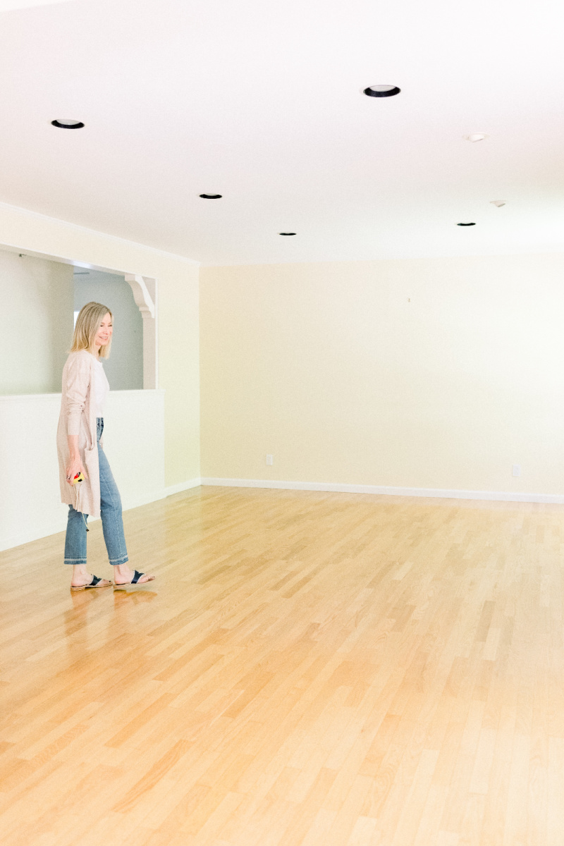 Woman standing in empty living room prior to renovation