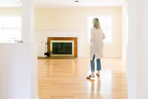 Woman looking into empty living room before renovation