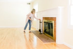 Woman looking at fireplace in empty room before renovation