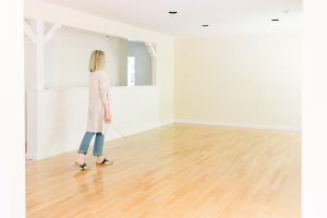 Woman standing in empty room before renovation