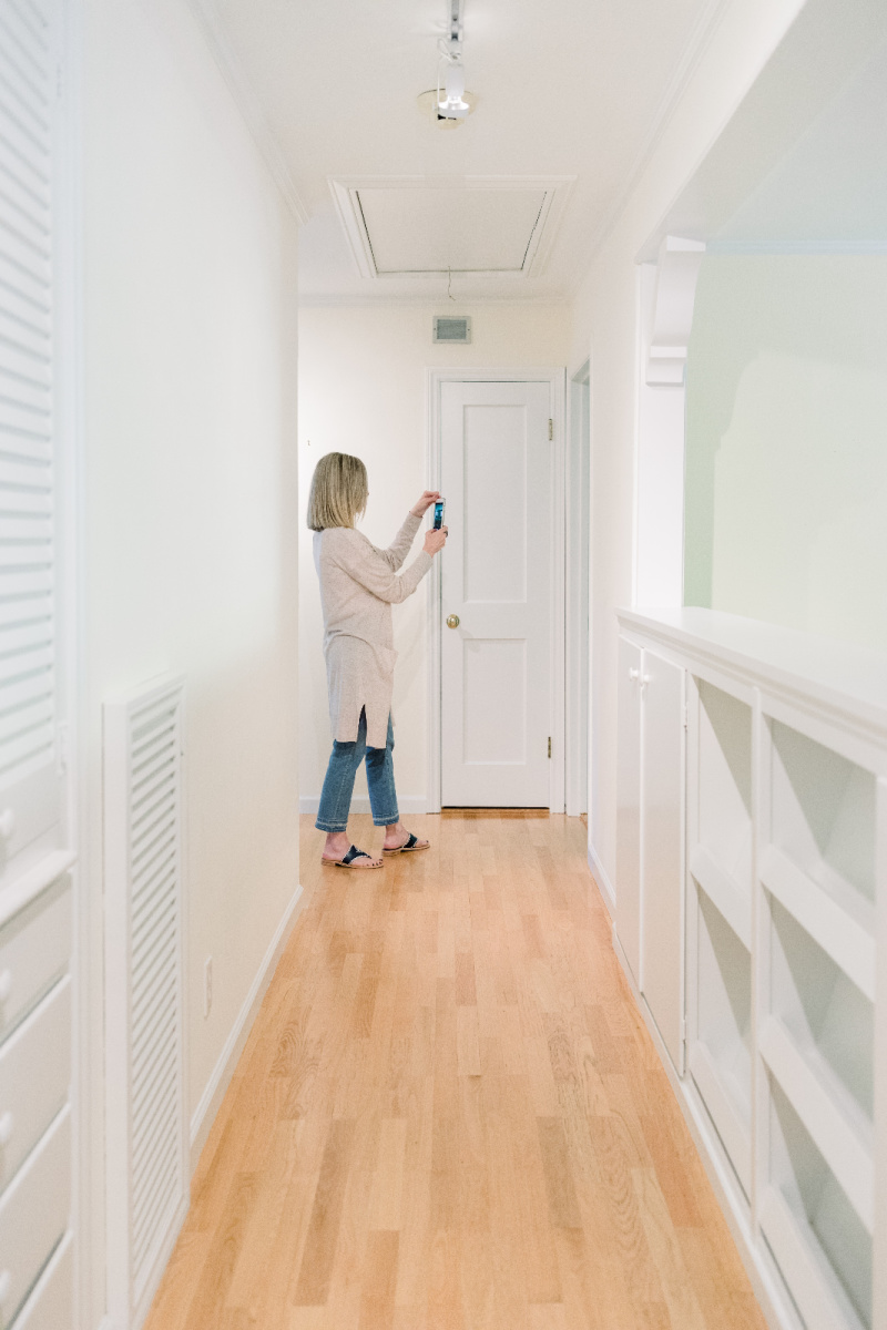 Woman at end of hallway taking pictures