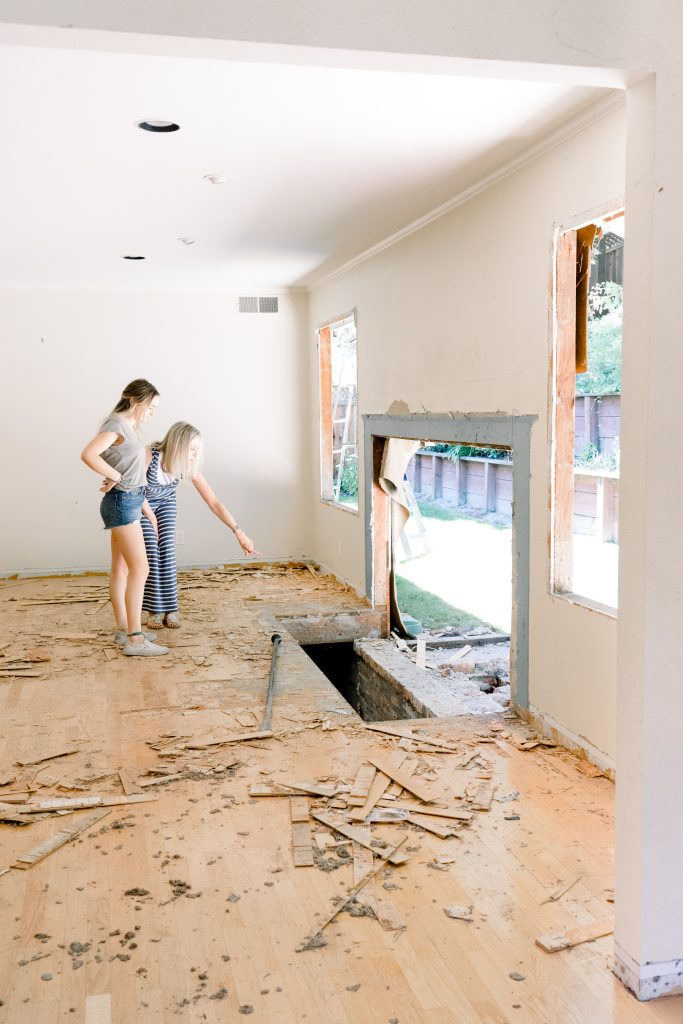 Two women looking at demolished fireplace
