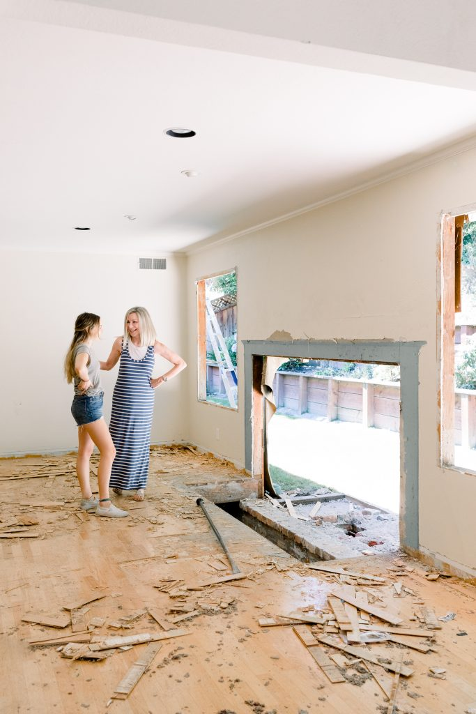Two woman looking at demolished fireplace