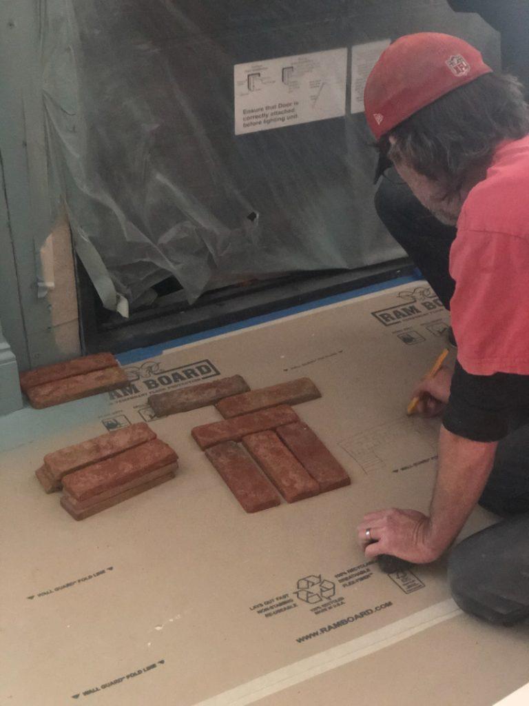 Man working on fireplace brick