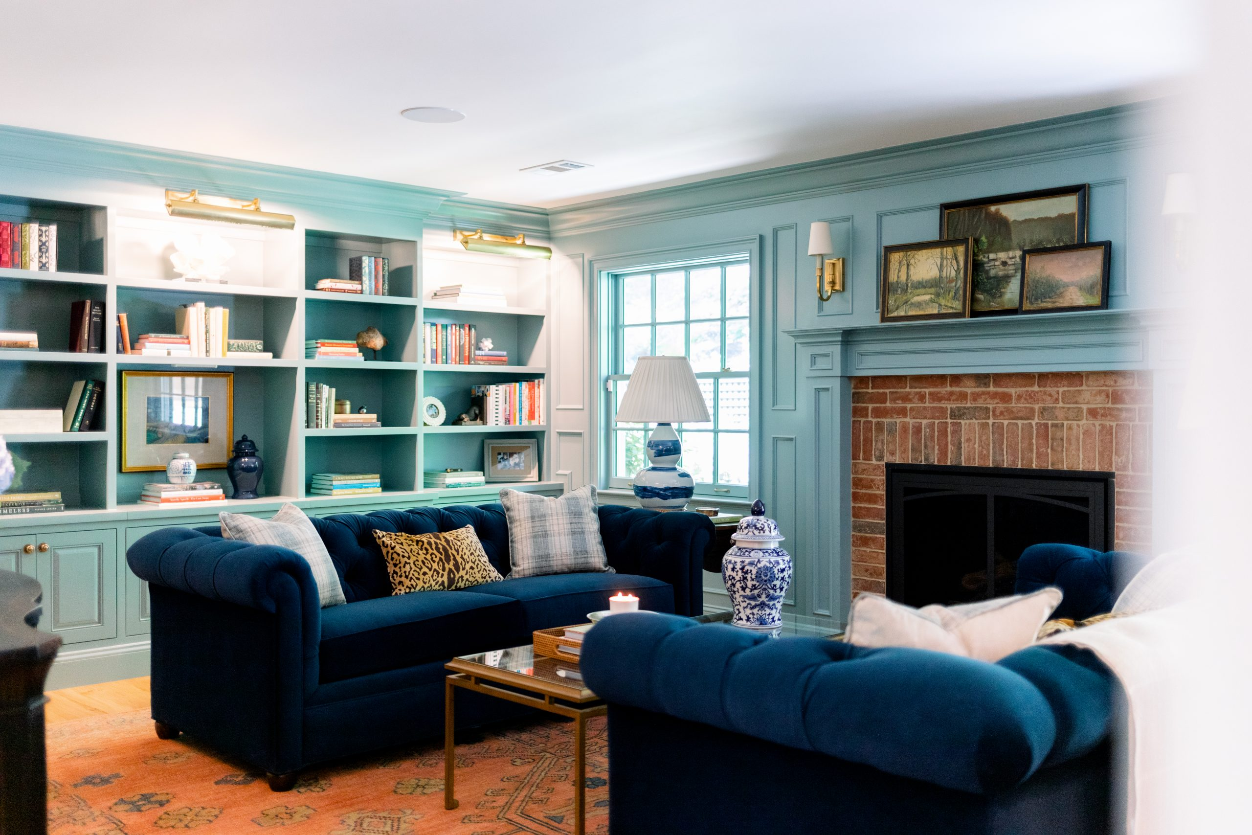 Home Library with blue velvet sofas and book shelves