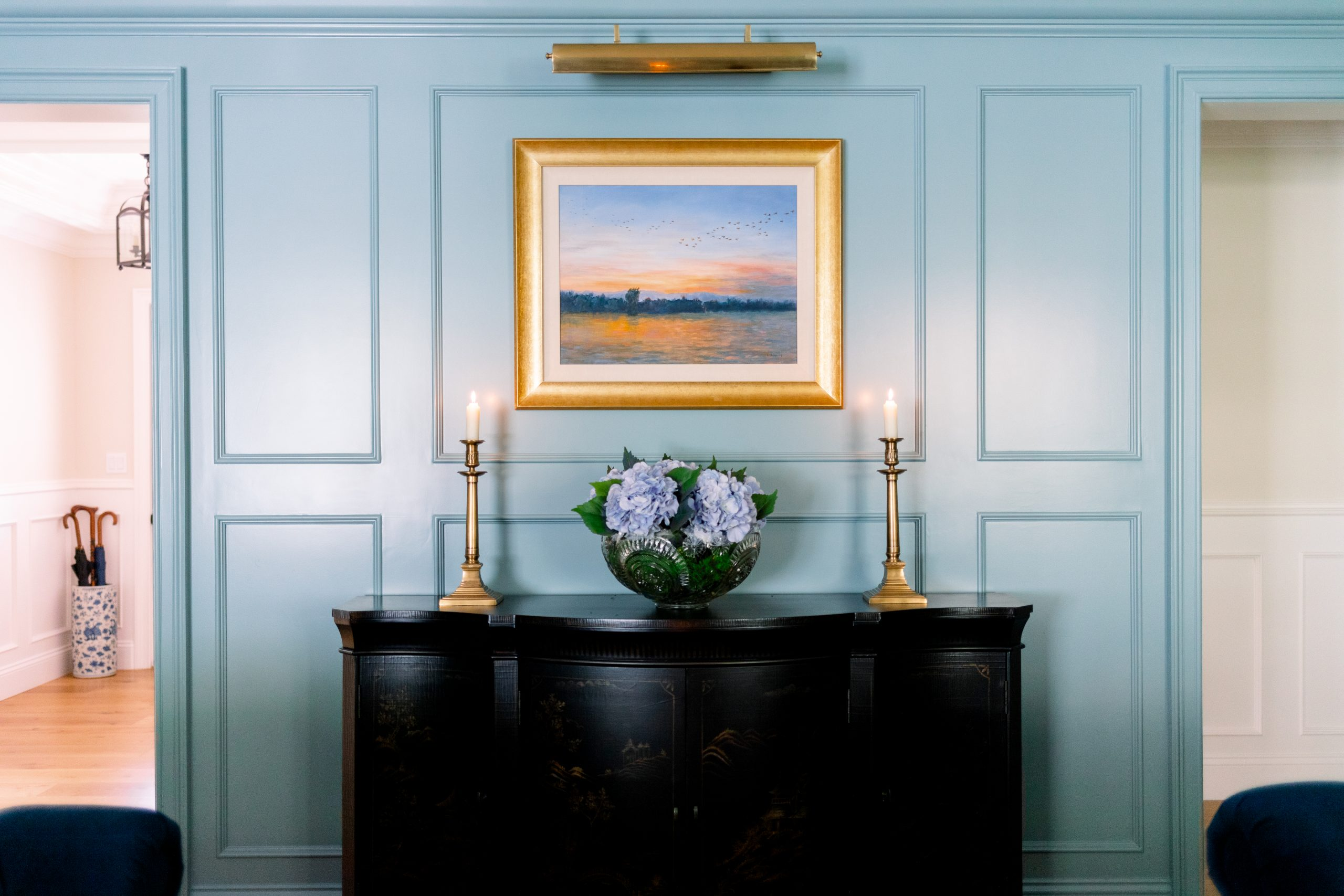 Blue Paneled Walls and black console cabinet