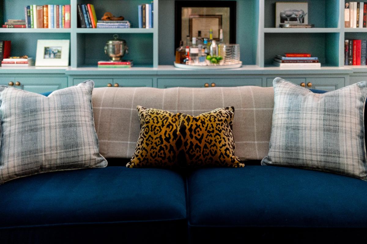 Blue velvet sofa with leopard print pillow