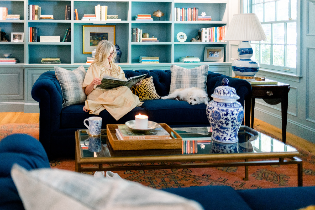 Woman reading book on blue velvet sofa with dog