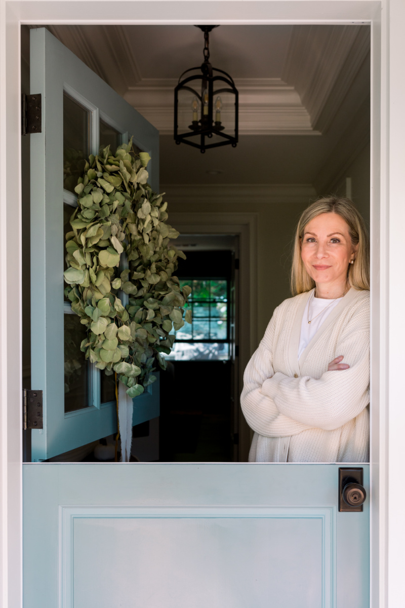 Woman standing inside blue Dutch door with eucalyptus wreath