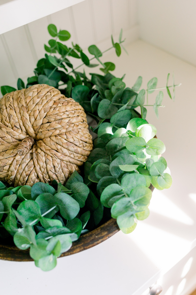 Eucalyptus leaves and woven pumpkin in wooden bowl