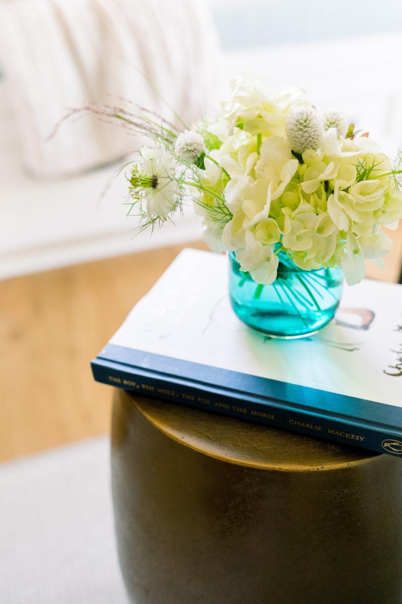 Book and floral arrangement on side table vignette