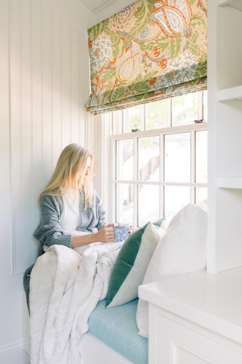 Woman sitting in window seat with mug