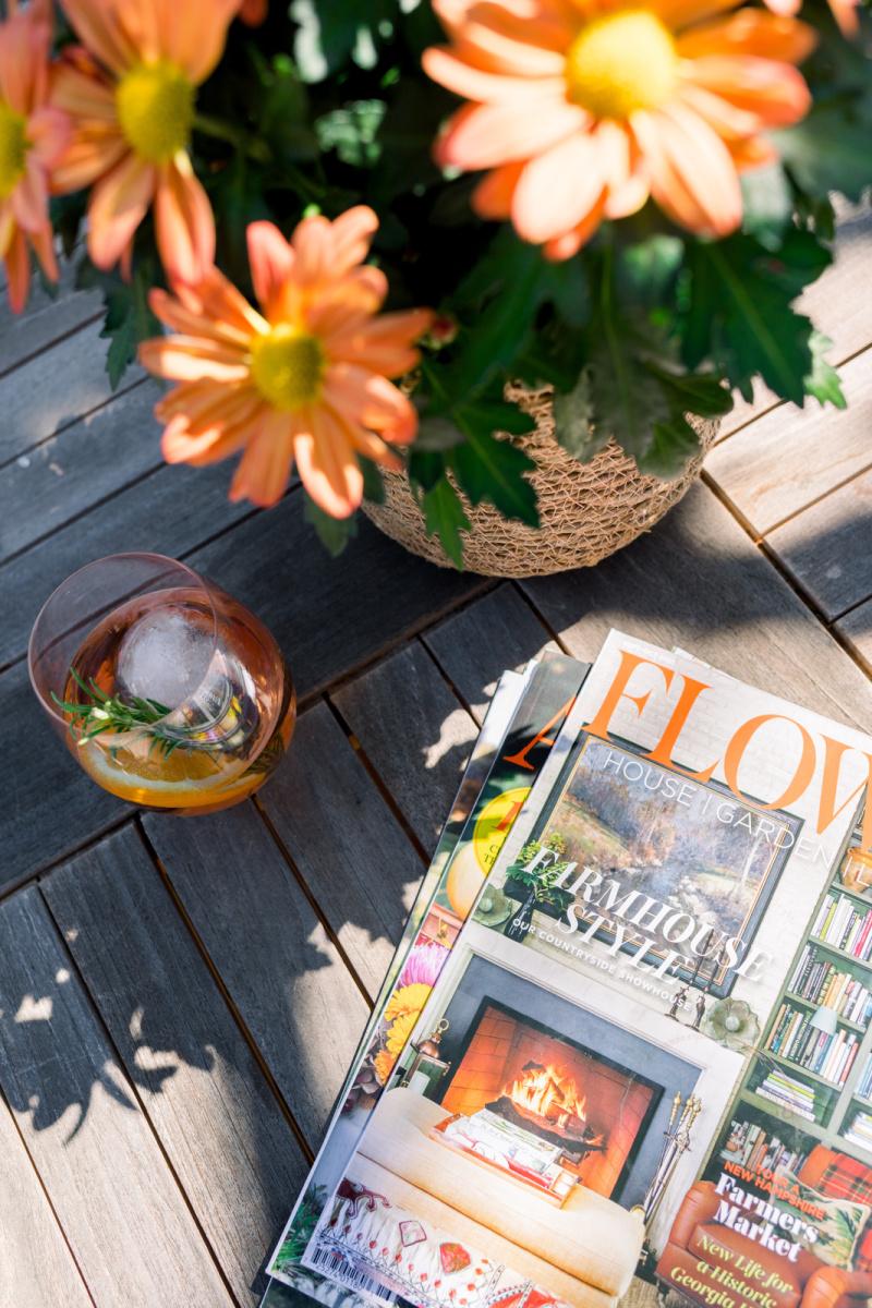 Wine glass flowers and magazines on teak table