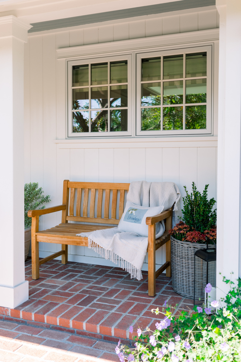 Teak bench on front porch decorated for fall