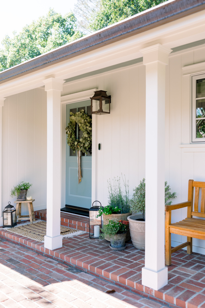 Front Porch and blue door decorated or fall