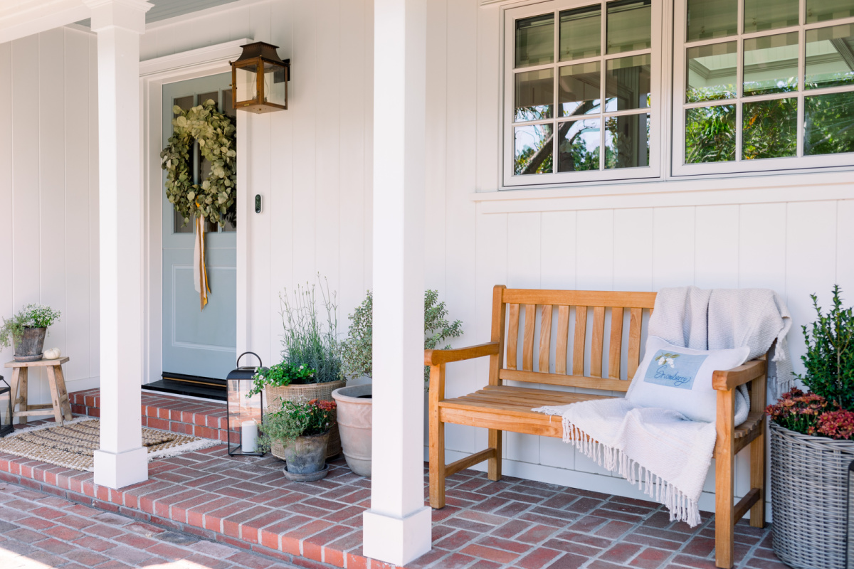 Front Porch bench and blue dutch door decorated for fall