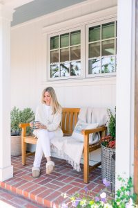Woman sitting on porch bench with coffee